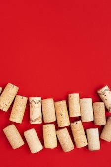 Gebrauchte weinkorken auf rotem papierhintergrund mit kopienraum. draufsicht mit holzkorken von der flasche wein.