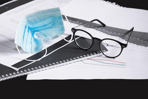 Gebrauchte zerknitterte medizinische maske, brille auf karte