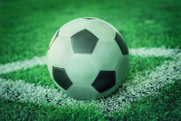 Gebrauchter klassischer schwarzweiss-fußball auf fußball-eckmarkierungsfeld ohne personen.