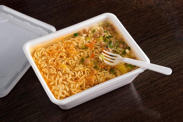 Gebraute instantnudeln in plastikverpackung, nahaufnahme, draufsicht, junk food, fast food
