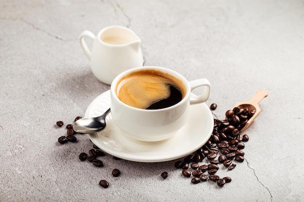 Gebrauter americano-kaffee in einer weißen tasse mit milch in einem krug auf dem konkreten hintergrund