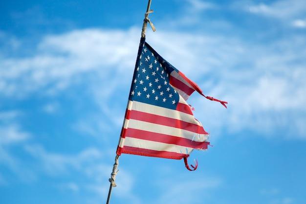 Gebrochene amerikanische flagge weht auf dem mast