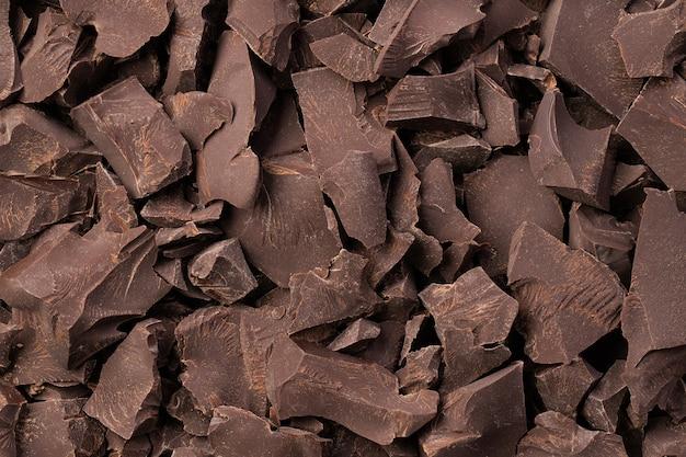 Gebrochene bars dunkler schokolade hintergrund, dessert essen