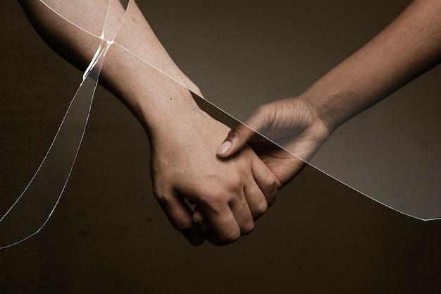 Gebrochene beziehung mit gebrochenem glaseffekt und menschen, die sich hinter den händen halten