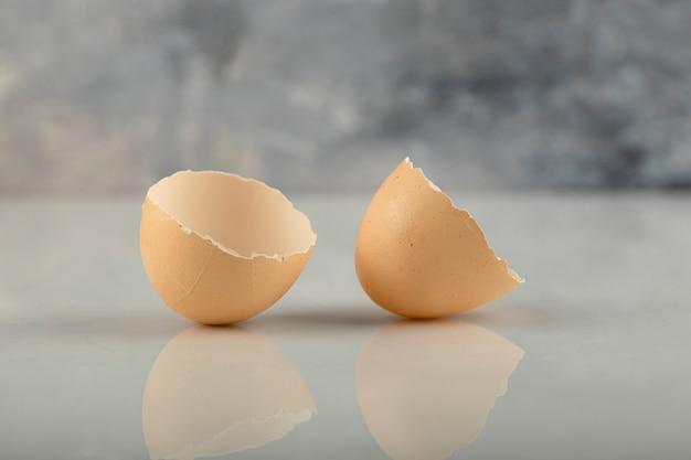 Gebrochene braune eierschale auf einer marmoroberfläche.