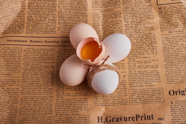 Gebrochene eier auf einem stück zeitung.