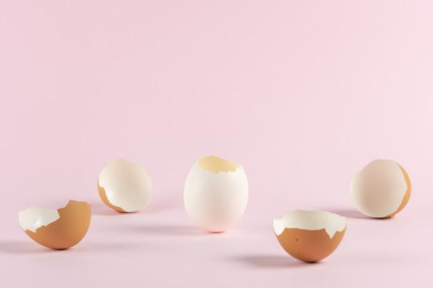 Gebrochene eierschale mit gebrochenen ostereiern gegen pastellrosa hintergrund