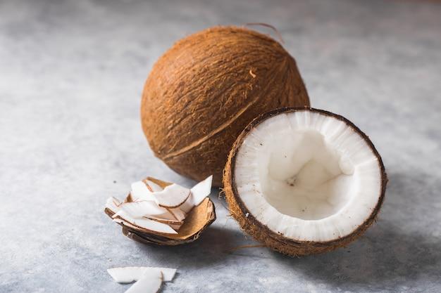 Gebrochene frische kokosnuss und scheibennuss auf konkretem hintergrund, platz für text lebensmittelzutaten, gesunder lebensstil, paradies