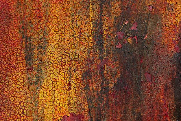 Gebrochene gelbe und rote farbe auf einer rostigen metallwand industrieller hintergrund