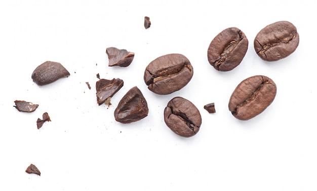 Gebrochene geröstete kaffeebohnen mit krümeln isoliert