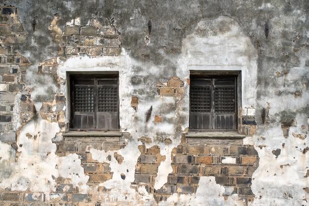 Gebrochene holzfenster und steinmauern