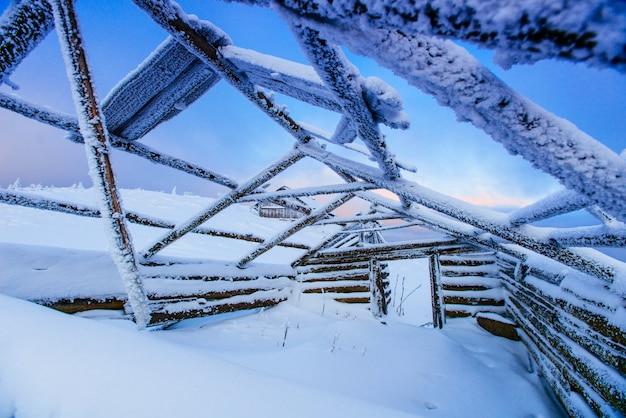 Gebrochene hütte aus der mitte mit schnee bedeckt
