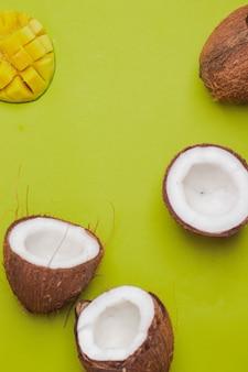 Gebrochene kokosnüsse mit mango auf grünem hintergrund. kreatives konzept. pop-art-essen. tropenfrucht flatlay mit copyspace