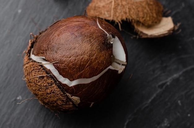 Gebrochene kokosnuss auf dunklem steinhintergrund