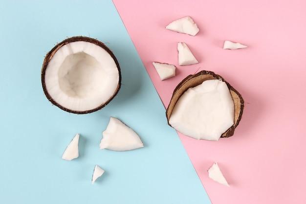 Gebrochene kokosnuss auf einer farbigen hintergrundansicht von oben