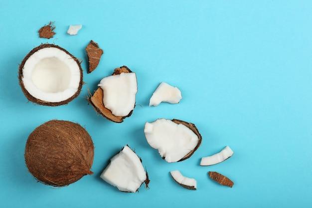 Gebrochene kokosnuss auf einer farbigen hintergrundnahaufnahme