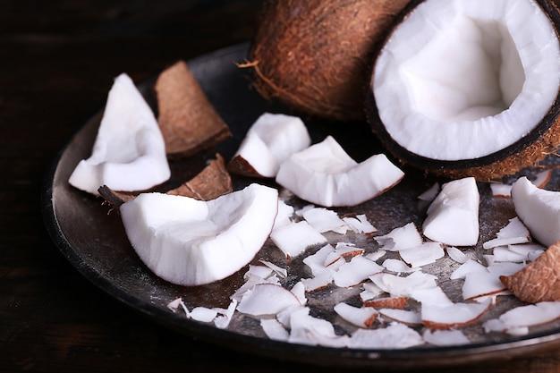 Gebrochene kokosnuss auf metallplatte auf rustikaler hölzerner tischoberfläche