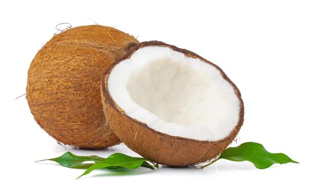 Gebrochene kokosnuss mit den blättern getrennt auf weiß