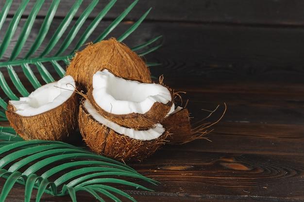 Gebrochene kokosnussstücke auf dunklem hölzernem