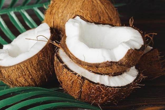 Gebrochene kokosnussstücke auf dunklem holz