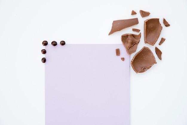 Gebrochene schokolade mit leerem papier auf tabelle