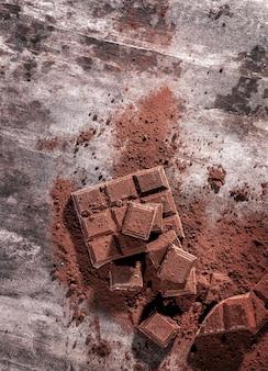 Gebrochene schokoladenstücke und kakaopulver auf holzuntergrund