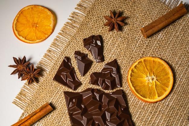 Gebrochene tafel schokolade in der nähe einer tasse zimt und orangentee