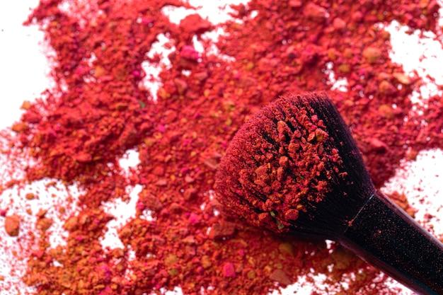 Gebrochene, verstreute mischung aus lidschatten mit make-up-pinsel auf weiß