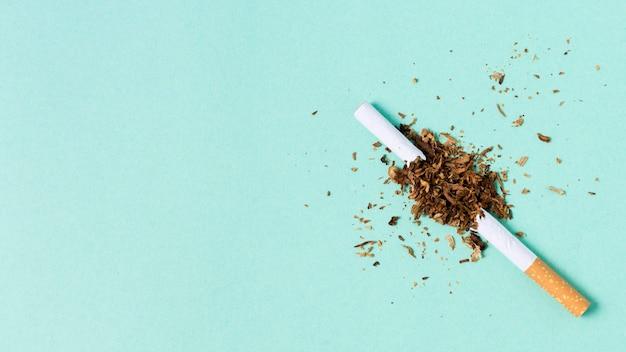 Gebrochene zigarette auf grünem hintergrund