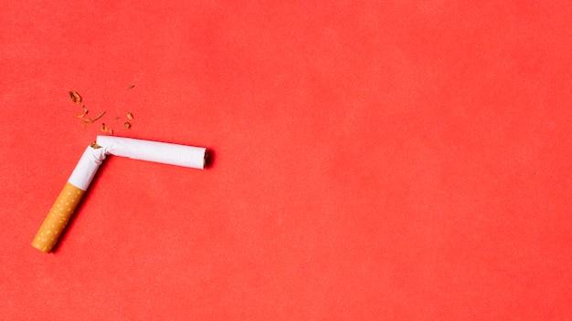 Gebrochene zigarette auf rotem hintergrund