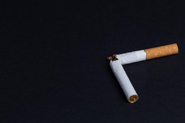 Gebrochene zigarette auf schwarz