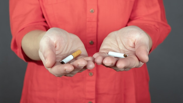 Gebrochene zigarette in weiblichen händen, aufhören zu rauchen zeichen.