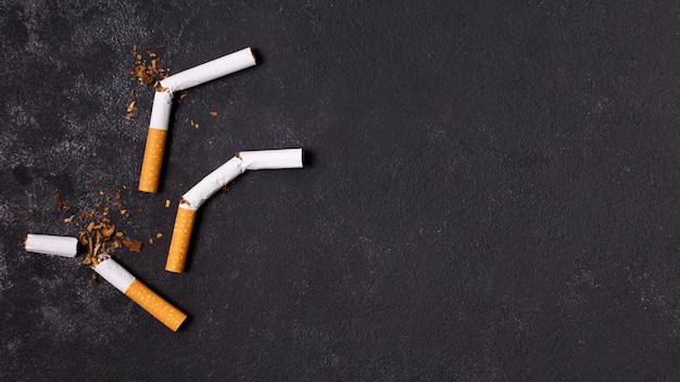 Gebrochene zigaretten auf stuckhintergrund