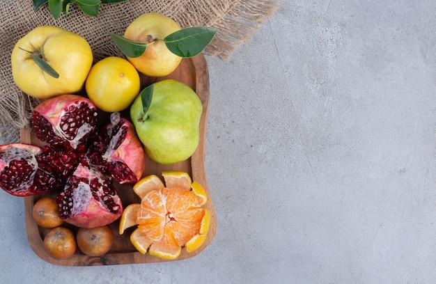 Gebrochener granatapfel, geschälte mandarine und ganze quitten und birnen auf einem stück stoff auf marmorhintergrund.