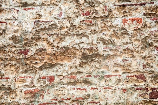 Gebrochener putz auf der mauer, schmutz aus braunen ziegeln