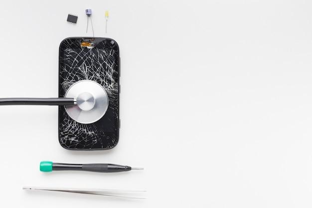 Gebrochener smartphone der draufsicht mit reparaturwerkzeugen