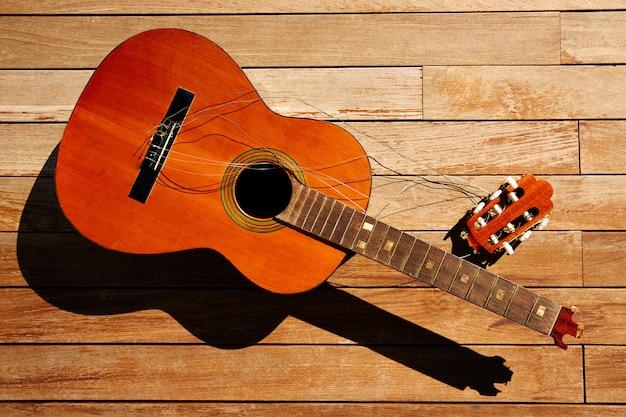 Gebrochener spanischer gitarrenhals auf hölzerner plattform