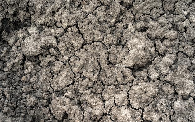 Gebrochener ton gemahlen in die trockenzeit-makroansicht auf hochauflösender, gerissener erde für hintergrund