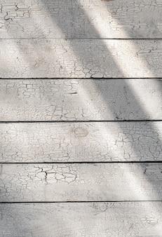 Gebrochener weißer hölzerner hintergrund schäbige verwitterte planken mit sonnenlicht, alte hell gemalte hölzerne brettweinlesebeschaffenheit, sonnenstrahlen auf rustikalem rauem unebenem schmutz der schuppigen struktur des rostigen tisches, vertikale draufsicht