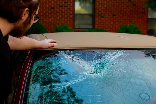 Gebrochenes autoglas mit fensterläden für unfall geknackt