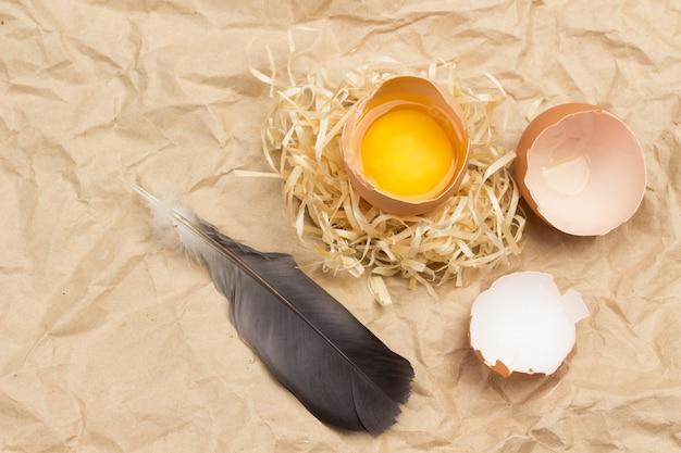 Gebrochenes ei auf stroh. eierschale und vogelfeder auf dem tisch. flach liegen