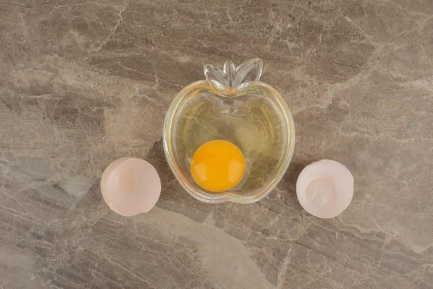 Gebrochenes ei auf teller auf marmortisch.
