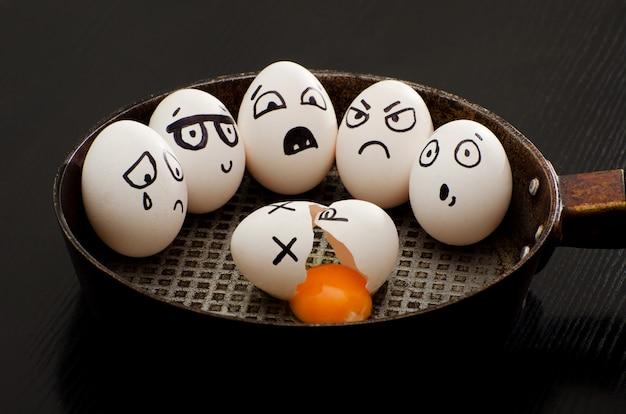 Gebrochenes ei in einer pfanne, umgeben von ganzen eiern mit verschiedenen emotionen