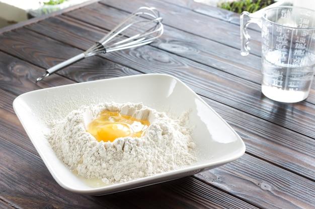 Gebrochenes ei in mehl in weißer platte, metallbesen, messglas mit wasser. sonnenstrahlen auf dem tisch, draufsicht, nahaufnahme