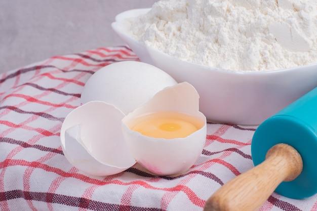 Gebrochenes ei, nudelholz und mehlschale auf tischdecke.