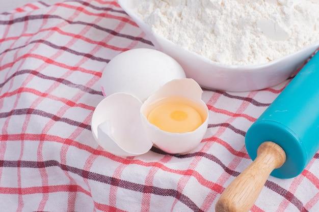 Gebrochenes ei, nudelholz und schüssel mehl auf tischdecke.