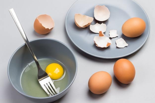 Gebrochenes ei und gabel in grauer schüssel. hühnerschalen auf grauem teller. zwei braune eier auf dem tisch. grauer hintergrund. draufsicht