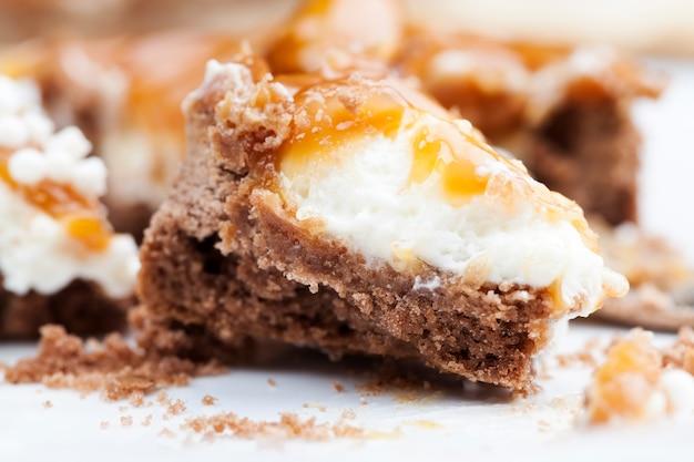 Gebrochenes geteiltes törtchen mit milchkäsefüllung und viel gesalzenem karamell mit nüssen, mandeln auf törtchen mit hüttenkäse oder buttercreme und karamell, leckere desserts zu den mahlzeiten