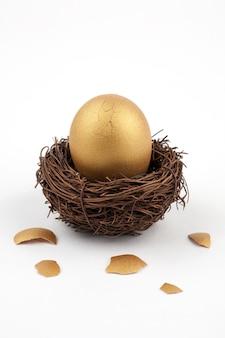 Gebrochenes goldenes ei auf weiß