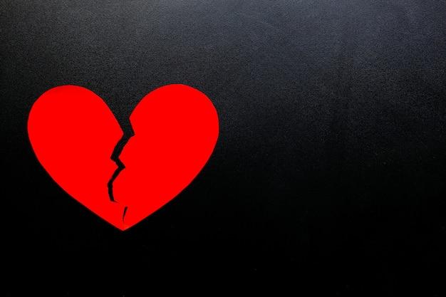 Gebrochenes herz aus rotem papier auf schwarzem hintergrund, repräsentieren liebe.